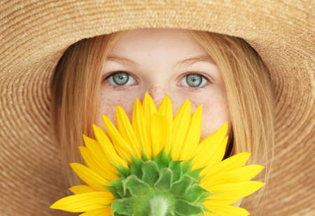 Portrait of attractive girl in straw hat with sunflower, close up