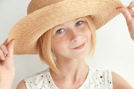 Portrait of cheerful teenager girl in straw hat on white background