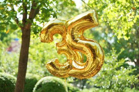 Golden birthday balloons on green background