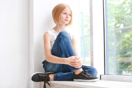 Cute teenager girl sitting near window