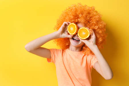 Funny girl in fancy wig holding orange on yellow background