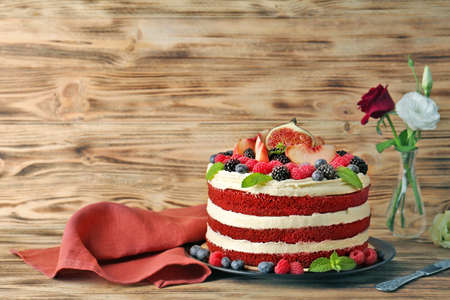 Tasty cake with berries and flowers on wooden background