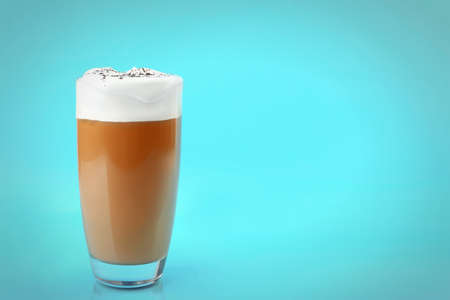 Glass of coffee with cream foam and cocoa powder on blue background