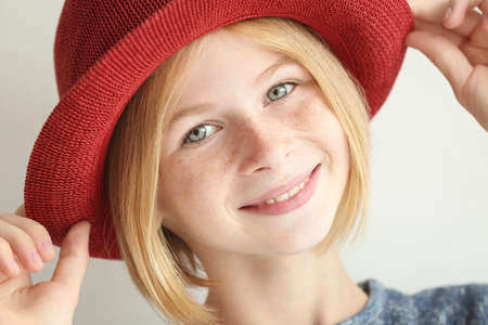Cheerful teenager girl with red hat on white background