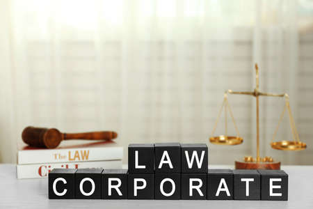 Black cubes with phrase LAW CORPORATE on white table