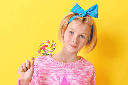 Funny teenager girl holding colourful lollipop on yellow background Stock Photo