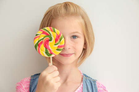 Funny teenager girl holding colourful lollipop on white background