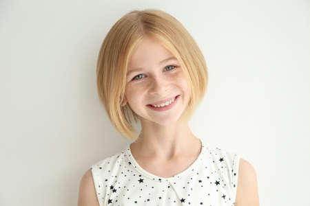 Portrait of cheerful teenager girl with freckles on white background