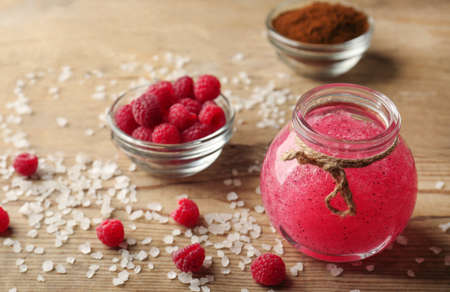 Body scrub, raspberry and coffee on wooden background