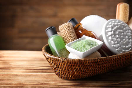 Set of body scrubs and bath accessories in basket on  wooden background