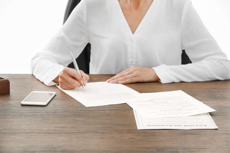 Successful businesswoman signing documents in office, close up view