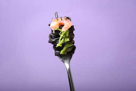 Fork with black pasta and shrimp on color background