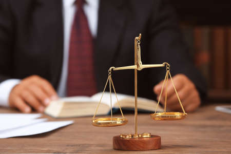 Scales of justice on wooden table and male lawyer on background Stock Photo