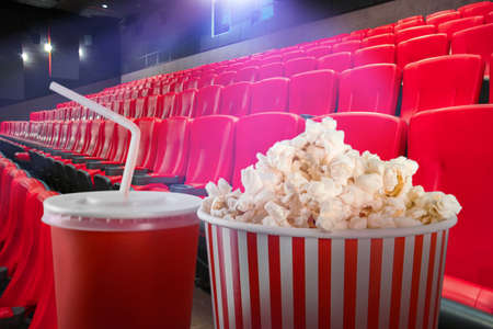 Tasty popcorn and cup of drink in cinema