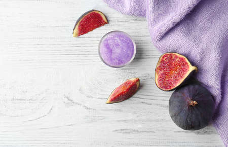 Body scrub and figs on wooden background