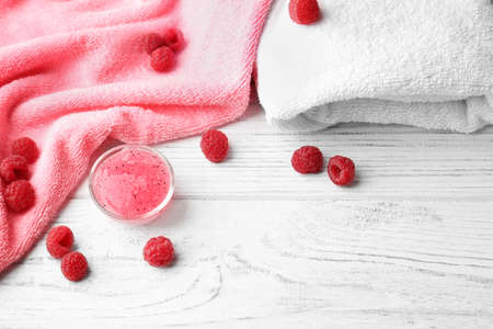 Body scrub in bowl, towels and raspberry on wooden background Stock Photo