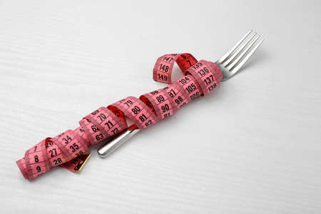 Fork with measuring tape on white wooden background
