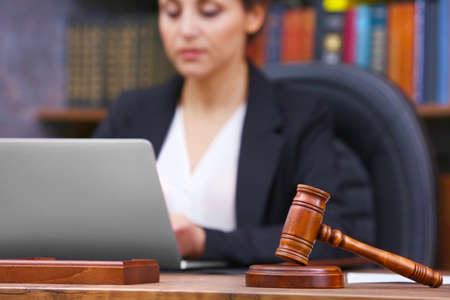 Brown gavel on wooden table and female lawyer on background, close up view Imagens