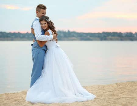 Beautiful wedding couple near river