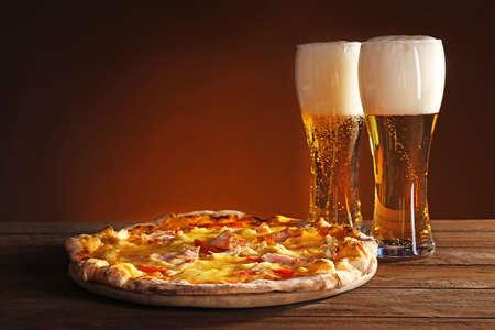 Sabrosa pizza con cerveza en la mesa de madera