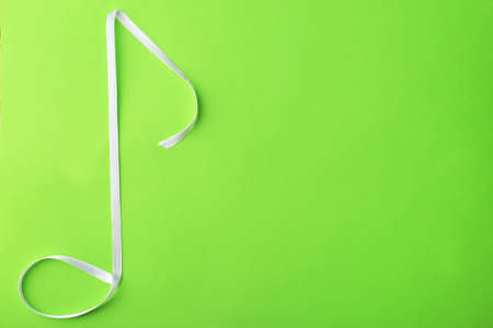 Musical note made of satin ribbon on green background Stock Photo
