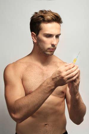 Muscular man holding syringe on white background Stock Photo