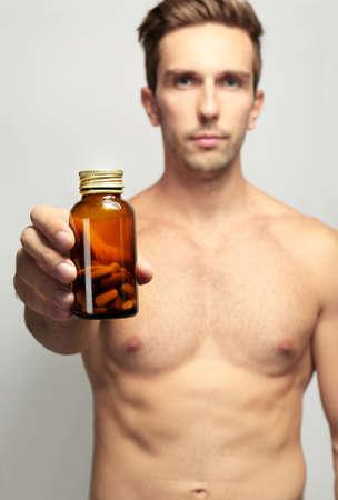 Muscular man holding drugs in bottle, closeup