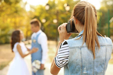 Young woman taking photo of happy wedding couple in park