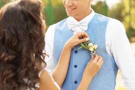 Die Braut steckt das Knopfloch fest, um die Weste zu pflegen