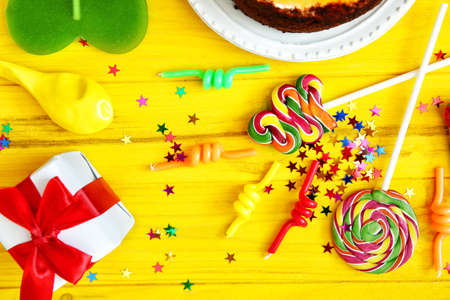 Birthday party objects on yellow wooden background, top view