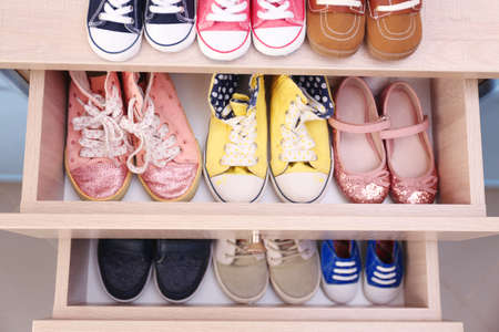 Different baby shoes in chest of drawers, top view