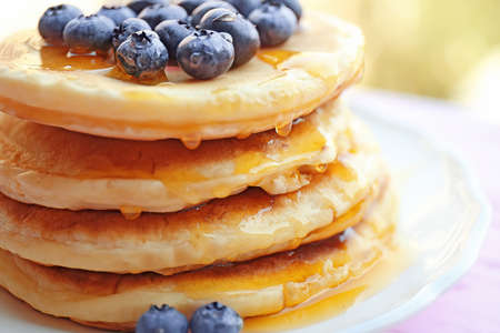 Stack of fresh pancakes with blueberry on plate closeup