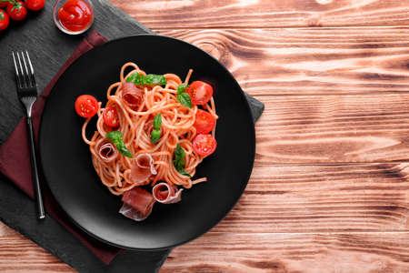 Spaghetti with amatriciana sauce and bacon on wooden table, top view