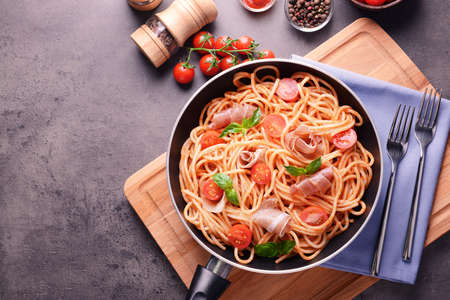 Spaghetti with amatriciana sauce and bacon in pan, top view