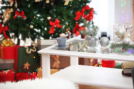 cup and glass vases with christmas decor on white table in living room decorated for christmas - How To Decorate Glass Vases For Christmas