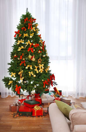 Beautiful Christmas tree and boxes with presents against window Stock Photo