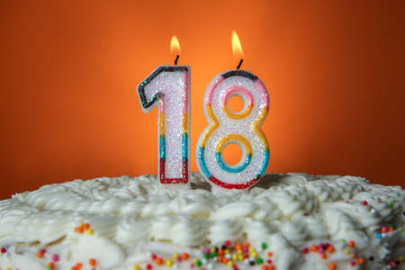 Tasty cake with candles for eighteenth birthday on orange background Stock Photo