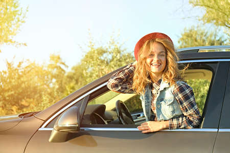 Young female driver in car on road trip