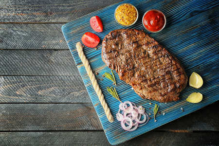 Delicious steak with spices on board and grey wooden background