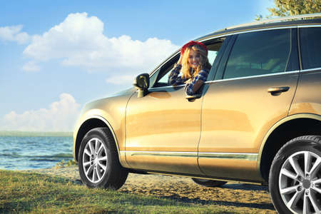 Young female driver in car on river shore Stock Photo