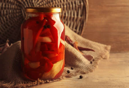 Canned red peppers in a jar on wooden background