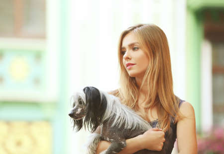 Beautiful young woman with her dog outdoors