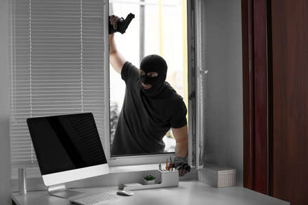 Thief with gun entering office through window