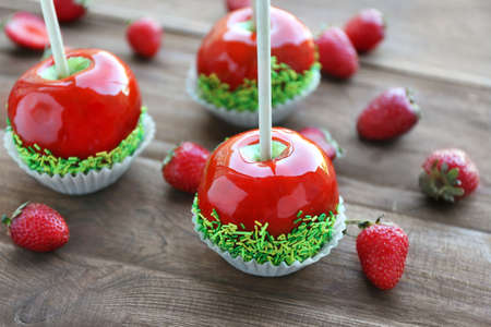 Candy apples with strawberry on wooden background Stock Photo