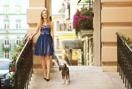 Beautiful young woman walking her dog outdoors