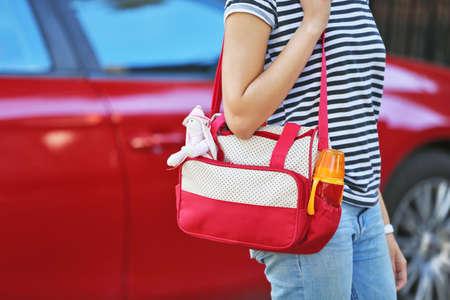 Femme, bébé, sac, debout, voiture