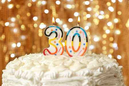 Birthday cake with candles on bokeh background Stock Photo