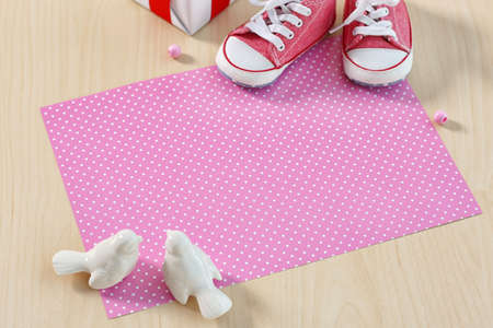 Composition with little baby shoes on wooden background