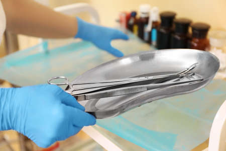 Doctor holding tools in steel basin, close up
