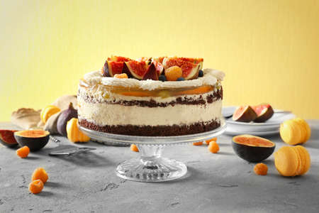 Delicious creamy cake with figs and berries on yellow textured background